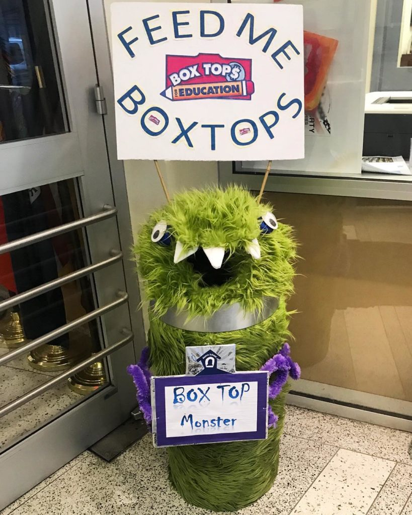 Photo of a green monster with mouth open holding a sign that says feed me boxtops